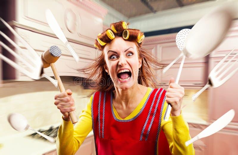 Dona de casa louca no avental que cozinha, voo do cookware imagens de stock