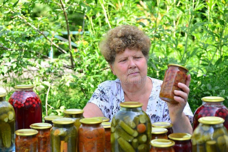 Dona de casa madura com umas conservas alimentares para o inverno imagem de stock
