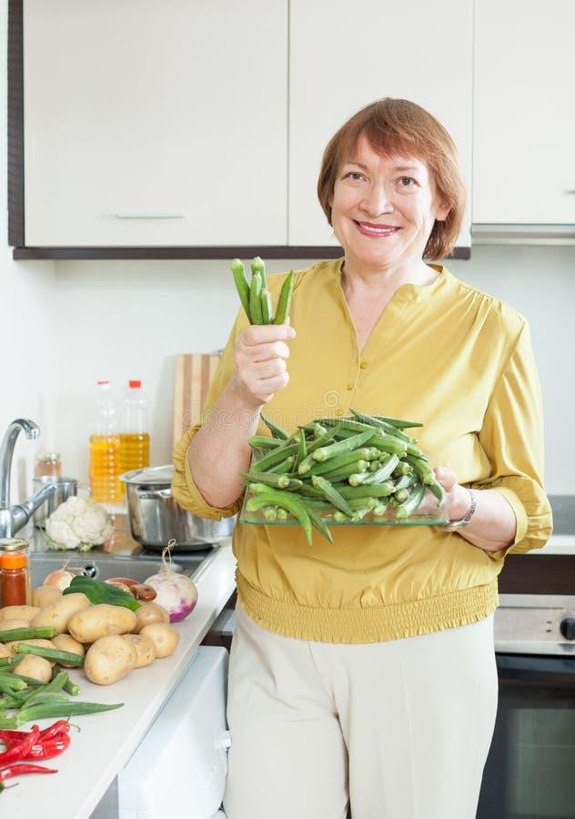 Dona de casa madura de sorriso que cozinha vegetais fotografia de stock