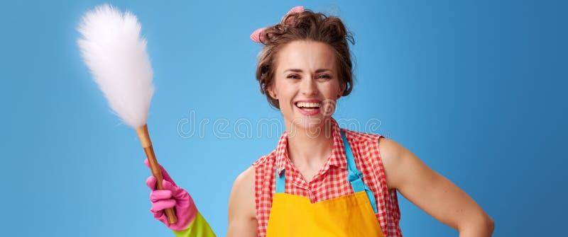 Dona de casa moderna feliz com a escova do espanador no azul foto de stock