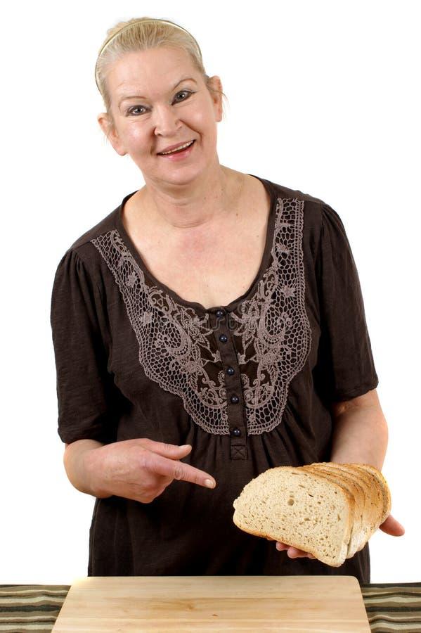 A dona de casa mostra algumas fatias de pão foto de stock royalty free