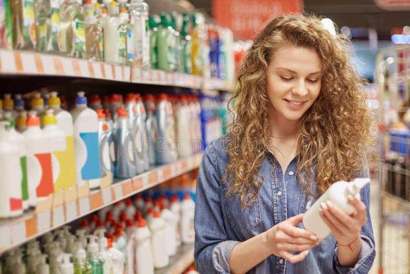 A dona de casa nova com olhar consideravelmente atrativo, escolhe produtos do agregado familiar ou detergente para a casa de limp fotografia de stock