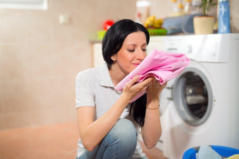 A dona de casa nova está fazendo a lavanderia com máquina de lavar imagens de stock