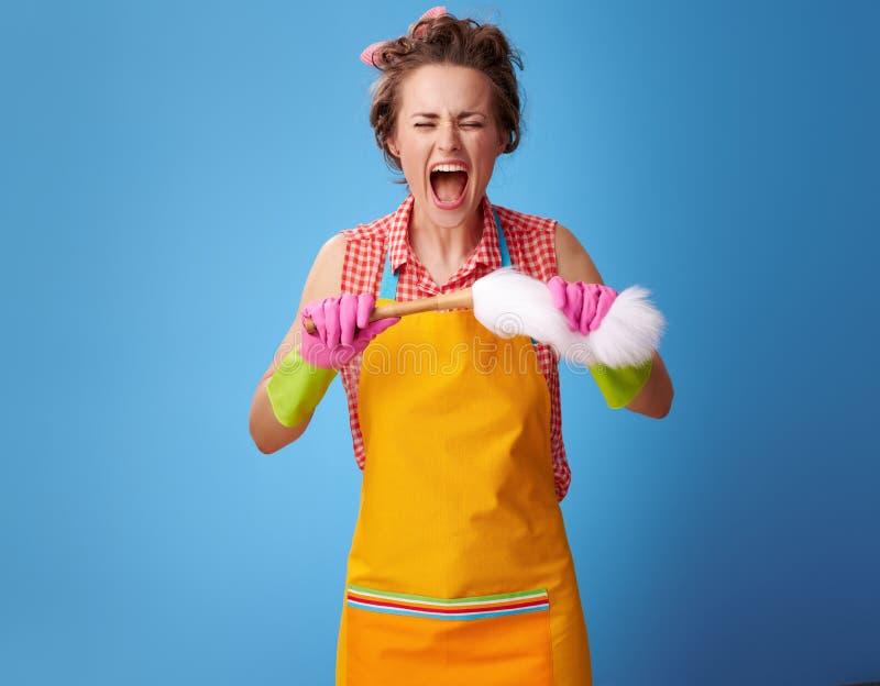 Dona de casa nova irritada que quebra a escova do espanador no azul fotos de stock royalty free