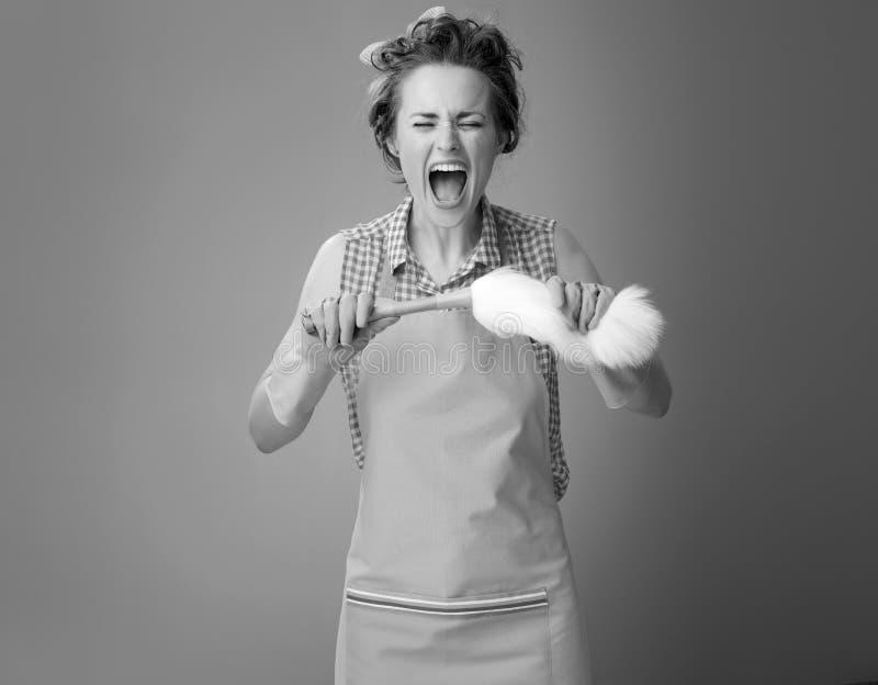 Dona de casa nova irritada que quebra a escova do espanador sobre imagens de stock royalty free