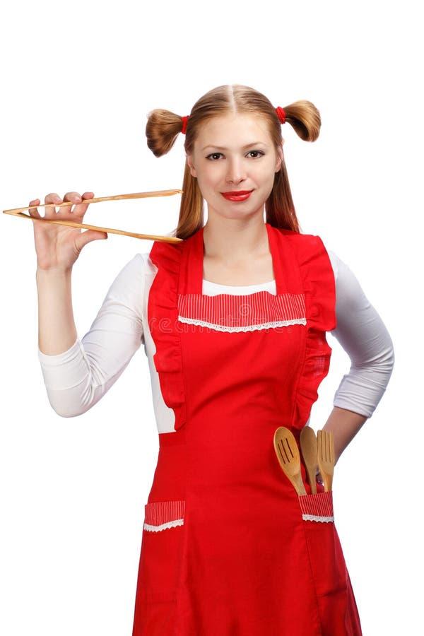 Dona de casa nova no avental vermelho brilhante com guardar engraçado dos rabos de cavalo fotos de stock royalty free