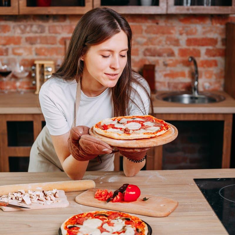 Dona de casa nova que cozinha a pizza em sua cozinha fotografia de stock royalty free