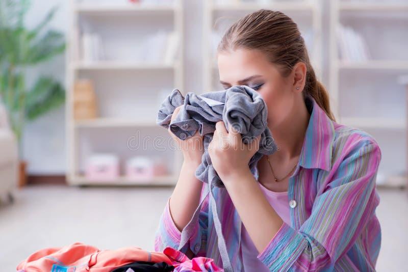 A dona de casa nova que faz a lavanderia em casa imagem de stock