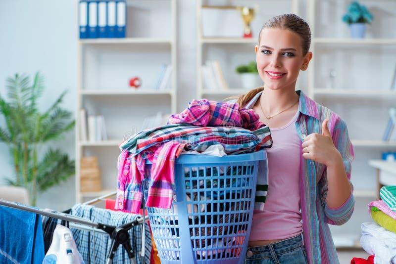 A dona de casa nova que faz a lavanderia em casa fotografia de stock