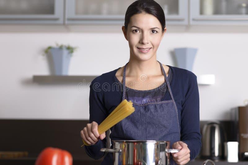 Dona de casa nova que prepara uma massa italiana saudável imagem de stock