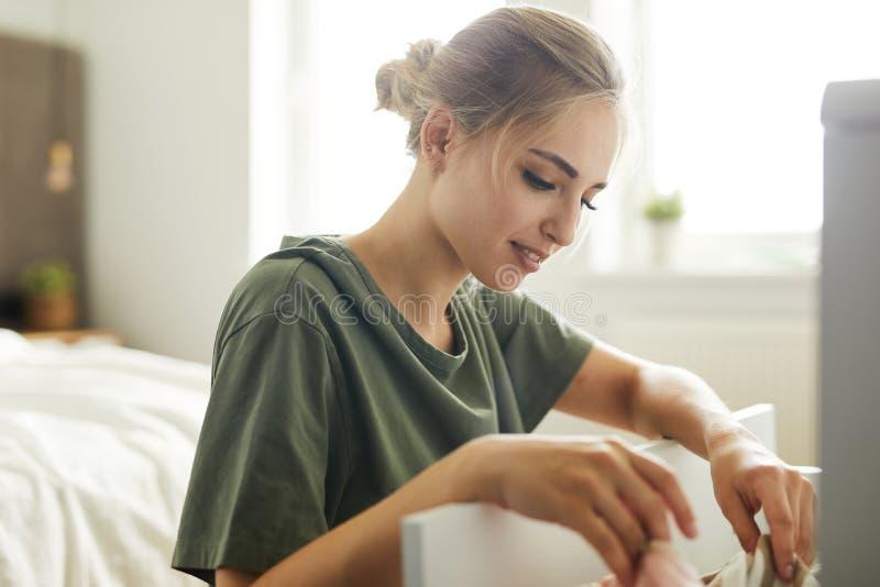 Dona de casa nova que senta-se pela gaveta aberta ao fazer o trabalho sobre a casa fotos de stock royalty free