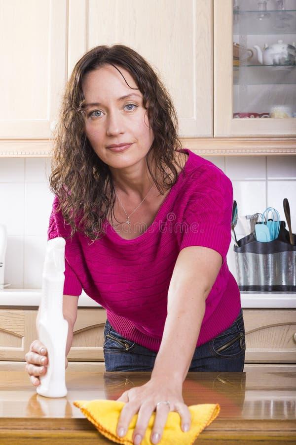 Dona de casa nova que sorri e que lustra fotos de stock