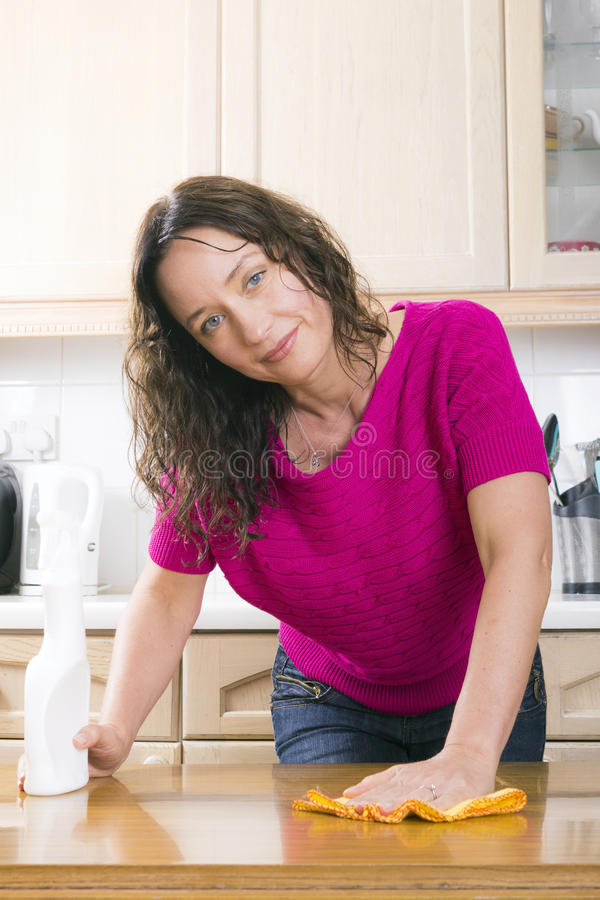 Dona de casa nova que sorri e que lustra foto de stock