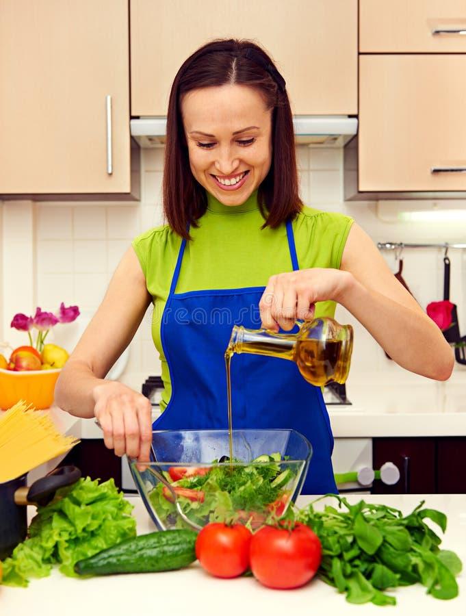 Dona de casa que adiciona o petróleo na salada imagem de stock royalty free
