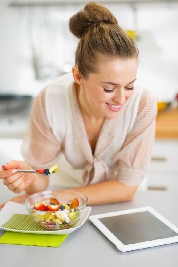 Dona de casa que come a salada de frutos e que usa o PC da tabuleta imagem de stock