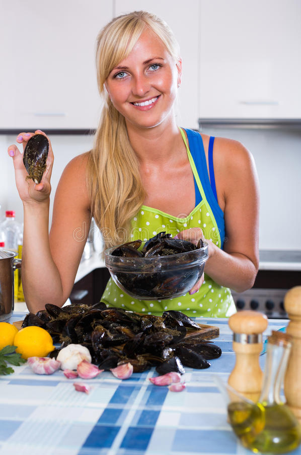 Dona de casa que cozinha moluscos em casa imagem de stock royalty free