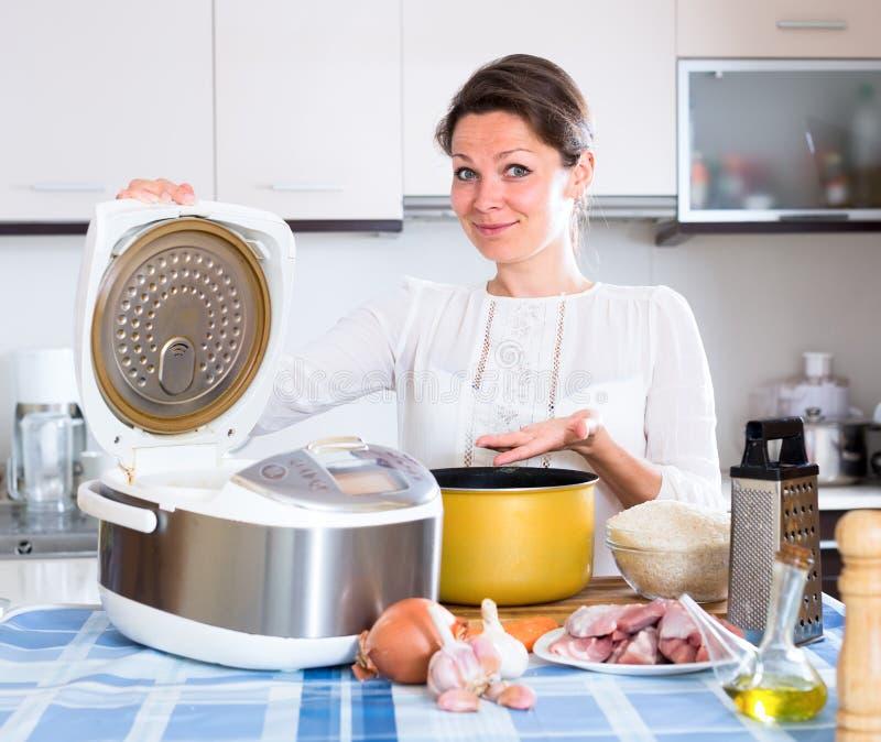 Dona de casa que cozinha o jantar no multicooker fotografia de stock royalty free