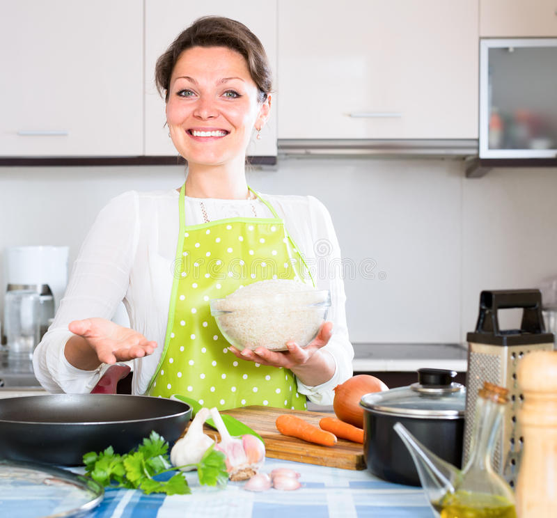 Dona de casa que cozinha o paella na cozinha imagem de stock