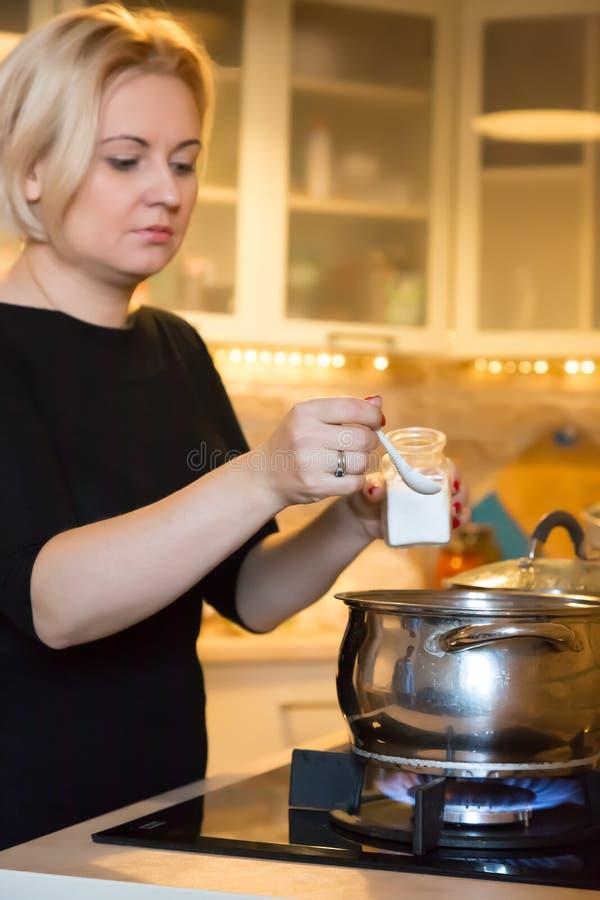 Dona de casa que cozinha a refeição no fogão de gás que adiciona ingredientes à bandeja de ebulição fotografia de stock royalty free