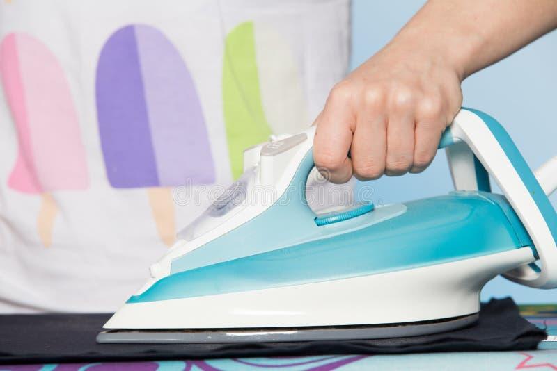 Dona de casa que faz trabalhos domésticos Opinião do close-up do ferro moderno na mão da mulher foto de stock royalty free