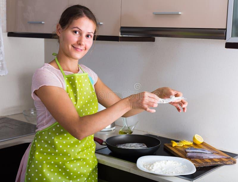 Dona de casa que frita peixes na cozinha fotos de stock