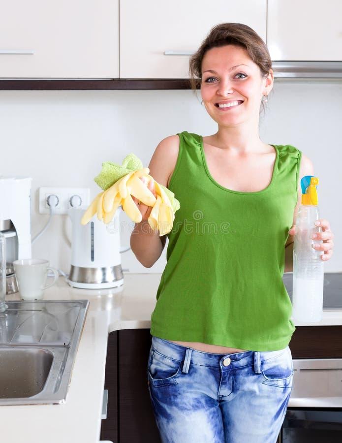 Dona de casa que guarda coisas da limpeza na cozinha foto de stock royalty free