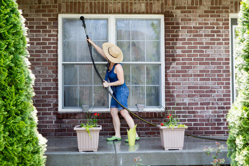 Dona de casa que lava as janelas de sua casa imagens de stock