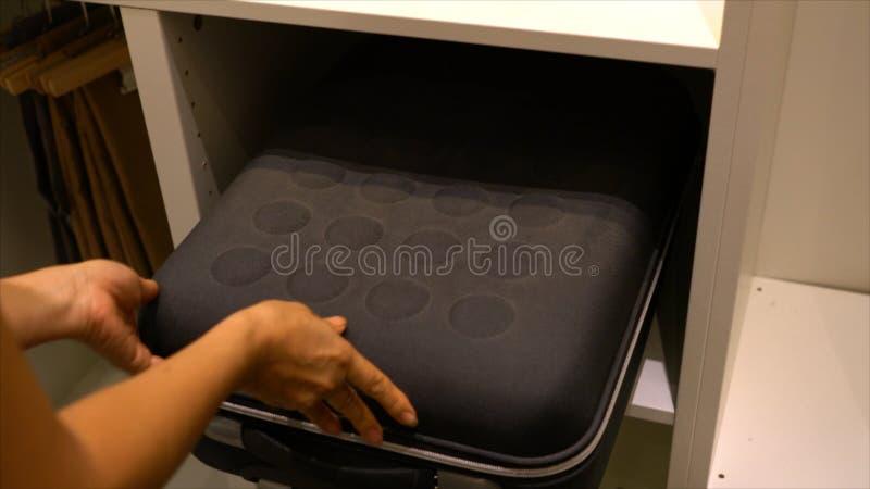 Dona de casa que mantém a mala de viagem preta em uma prateleira de loja branca imagem de stock