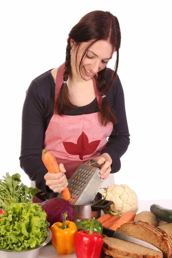 Dona de casa que prepara o almoço e que corta a cenoura fotografia de stock royalty free