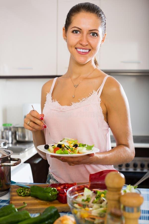 Dona de casa que prepara a salada com vegetais imagem de stock
