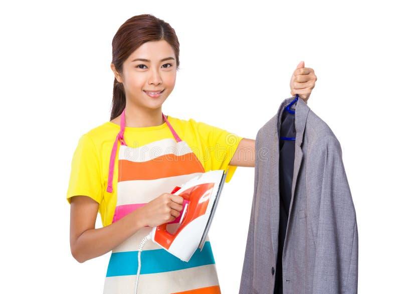Dona de casa que usa o ferro de vapor no revestimento do terno imagem de stock royalty free