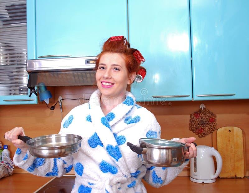 A dona de casa ruivo nova atrativa em um vestido de molho e sobre encrespadores de cabelo, na cozinha, mantém mercadorias da cozi fotografia de stock royalty free
