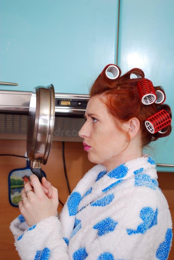 A dona de casa ruivo nova na cozinha que tem custos e olhares olhados de sobrancelhas franzidas na reflexão em uma frigideira imagem de stock royalty free