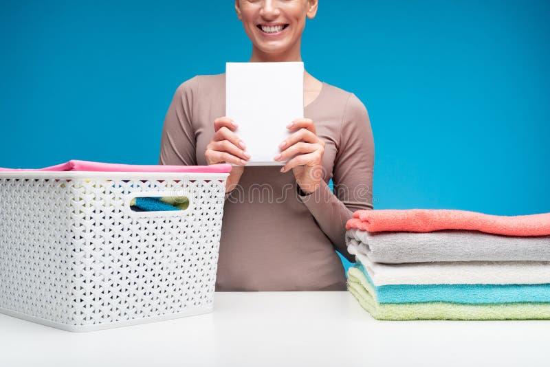 Dona de casa de sorriso com bloco do pó de lavagem fotografia de stock