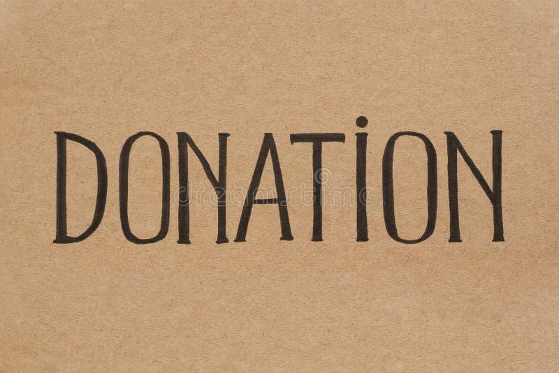 DONACIÓN de la palabra escrita a mano en la cartulina fotografía de archivo