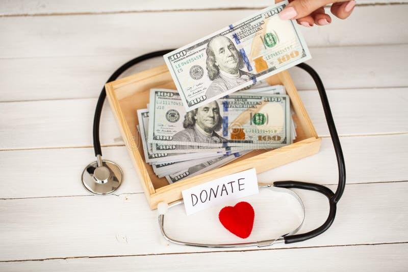 Donaciones y caridad Concepto de la donación Caja de donaciones y de corazón en el fondo blanco imágenes de archivo libres de regalías