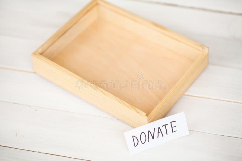 Donaciones y caridad Concepto de la donación Una caja de la donación en el fondo blanco La inscripción dona imagen de archivo libre de regalías