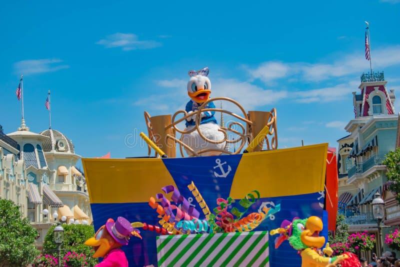 Donald Duck in de Verrassingsviering van Mickey en van Minnie paradeert op lichtblauwe hemelachtergrond in Walt Disney World 16 stock afbeelding