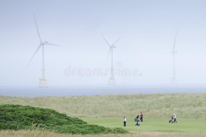 Donald Trump-golfcursus die de turbines en de golfspelers van het windlandbouwbedrijf in de Noordzee tonen royalty-vrije stock foto