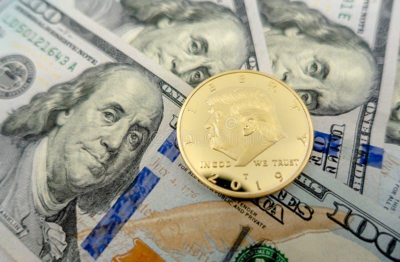 Donald Trump mynt mot en bakgrund av $100 räkningar arkivbild
