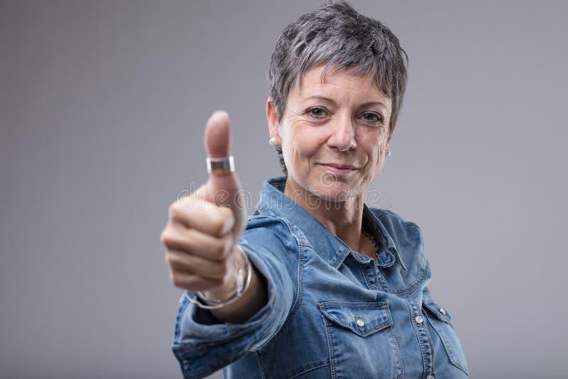 Donante de mediana edad sonriente de la mujer pulgares para arriba fotos de archivo