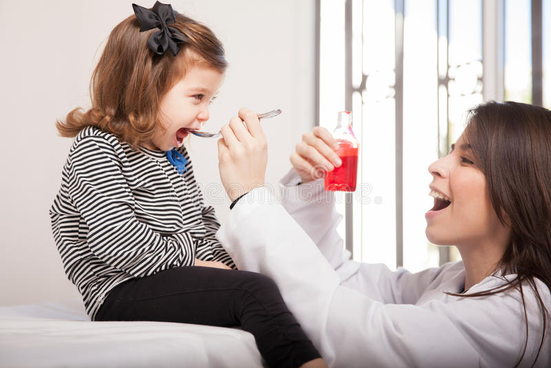 Donante del jarabe de la tos a una muchacha imagenes de archivo