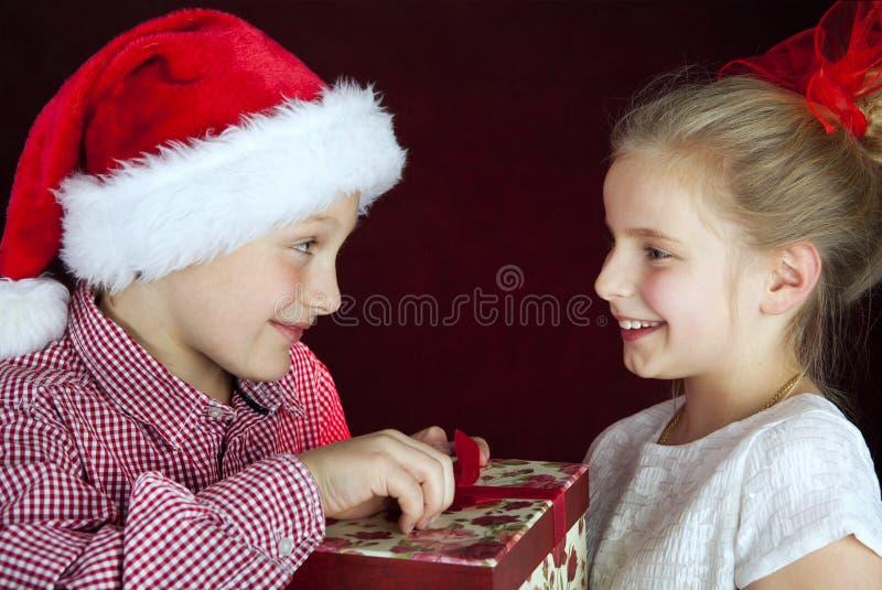 Donante del muchacho de la Navidad presente a la muchacha sonriente foto de archivo libre de regalías