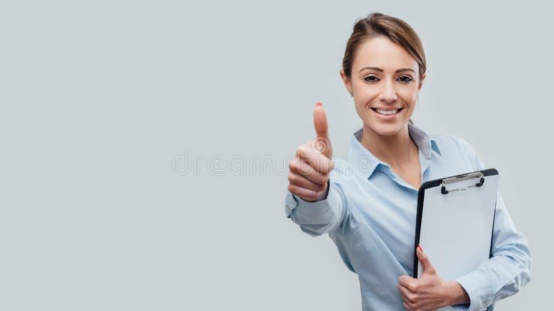 Donante femenino confiado del ejecutivo de operaciones pulgares para arriba imagen de archivo libre de regalías