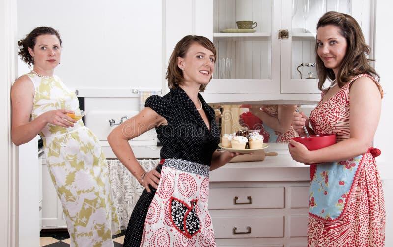 Donas de casa do vintage que cozem queques e tagarelice imagens de stock