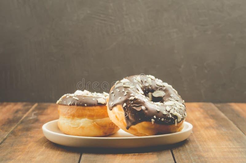 Donat Donat in der Schokolade wird mit zerriebenen Mandeln gestreut Donat in einer weißen Schüssel auf einem dunklen Hintergrund  stockbild
