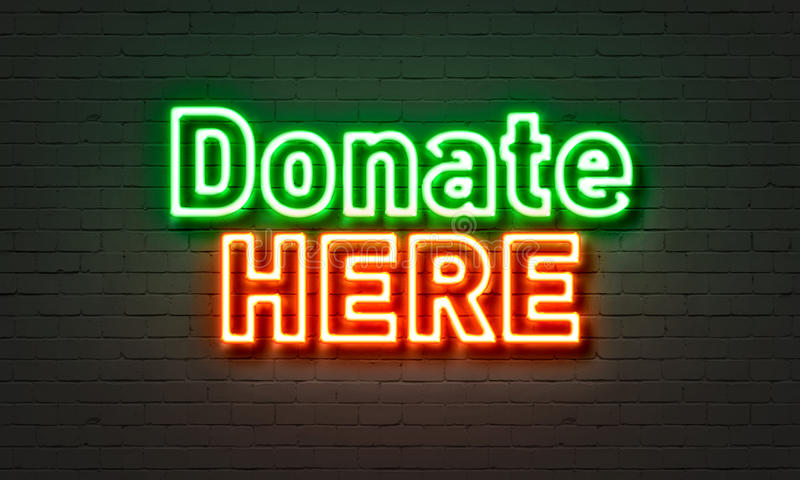 Donate here neon sign on brick wall background. royalty free stock image
