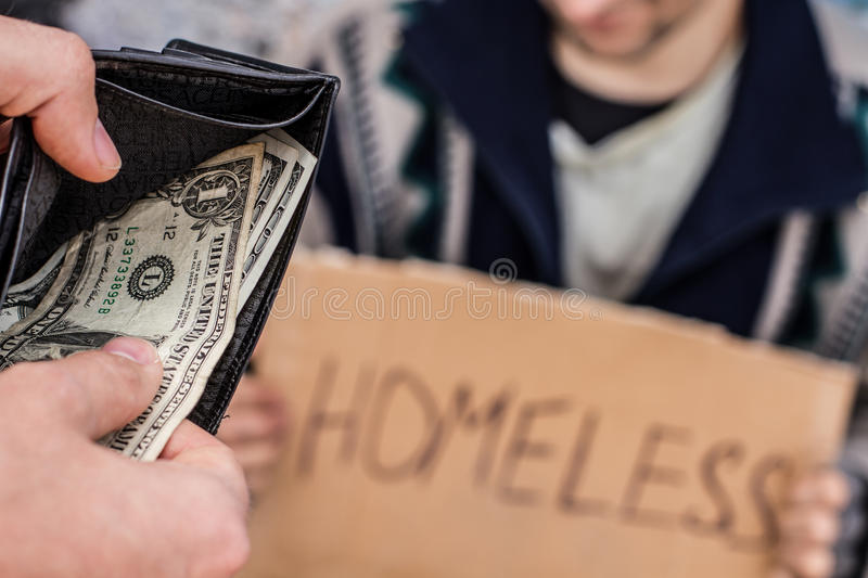 Donate for homeless. Someone is giving e few dollars to homeless man royalty free stock photo