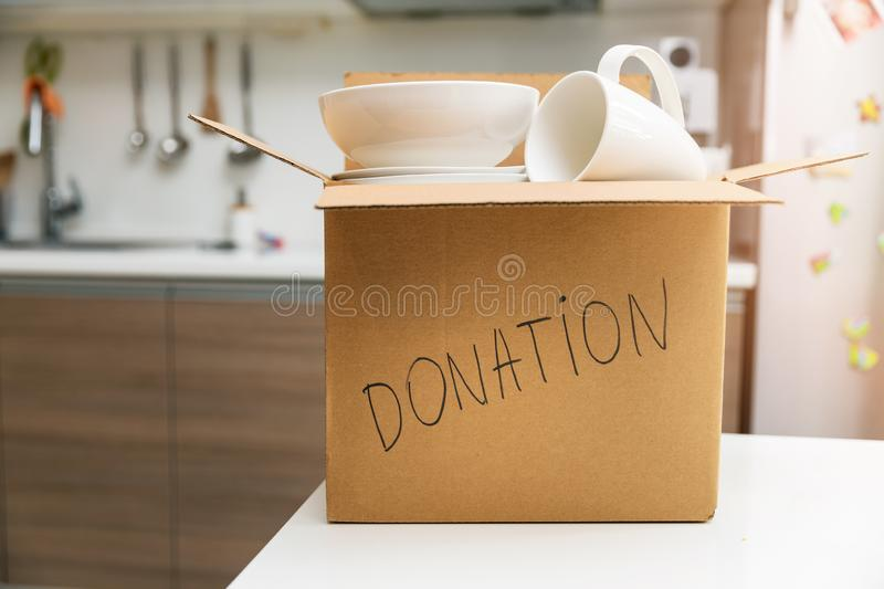 Donate household items - box with tableware for donation on kitchen table. Donate household items - cardboard box with tableware for donation on kitchen table stock photo