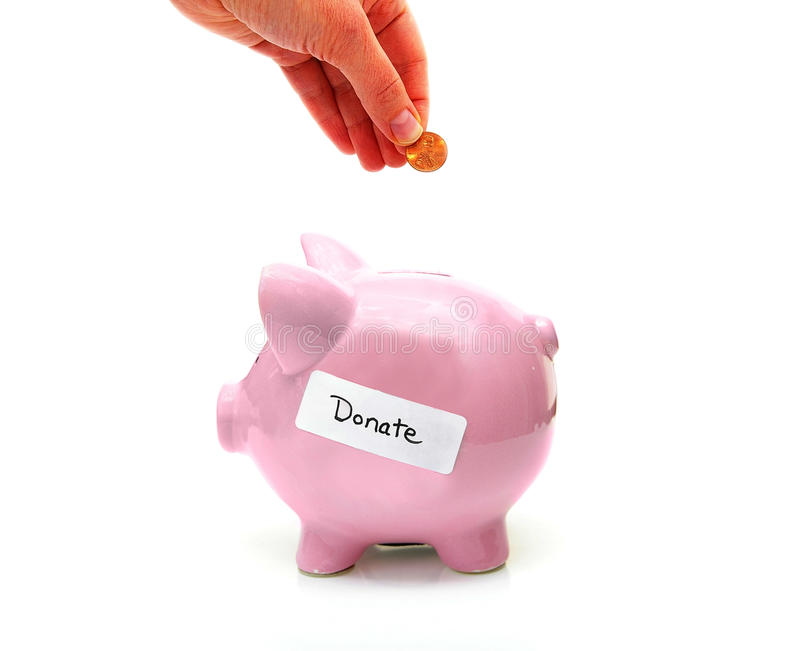 Donate money. Piggy bank with donate label and hand with penny royalty free stock images